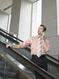 Businessman Using Mobile Phone On Escalator Royalty Free Stock Photo