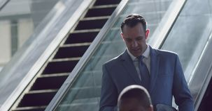 Businessman using mobile phone on escalator in a modern office 4k. Front view of Caucasian Businessman using mobile phone on escalator in a modern office 4k stock video footage