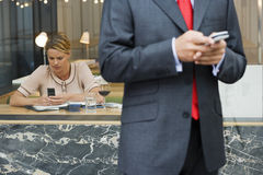 Businessman using mobile phone, focus on woman text messaging in background Stock Photos