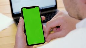 Businessman using mobile phone. With green chroma keyed screen against laptop and wooden table. Swiping, clicking and pinch gestures. Over the shoulder camera stock video