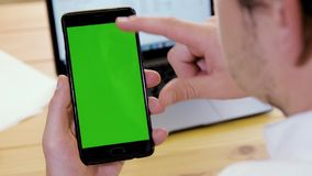 Businessman using mobile phone. With green chroma keyed screen against laptop and wooden table. Swiping, clicking and pinch gestures. Over the shoulder camera stock video footage