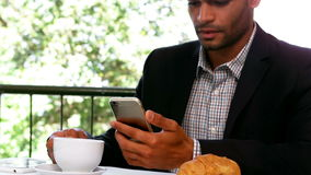 Businessman using mobile phone while having breakfast stock video footage