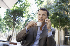 Businessman Using Mobile Phone While Having Coffee At Outdoor Ca Royalty Free Stock Images