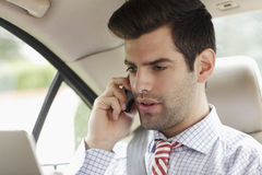 Businessman using mobile phone in his car Stock Images