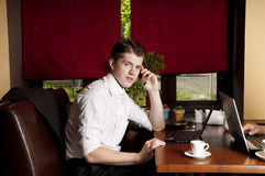 Businessman using a mobile phone and laptor  in cafe. Royalty Free Stock Photos