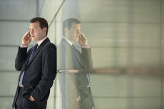 Businessman Using Mobile Phone While Leaning On Glass Wall Stock Images
