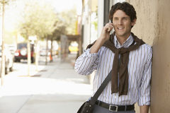 Businessman Using Mobile Phone While Leaning On Wall Stock Images