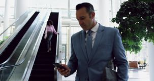 Businessman using mobile phone in the lobby at office 4k. Front view of Caucasian Businessman using mobile phone in the lobby at office. He is walking 4k stock footage
