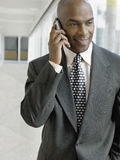 Businessman Using Mobile Phone While Looking Down In Office Royalty Free Stock Photography