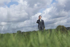 Businessman Using Mobile Phone In Meadow Royalty Free Stock Photography