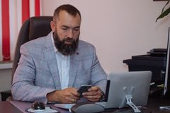 Businessman using mobile phone at office. Handsome bearded mature usinessman using mobile phone at office. Man sitting at table with tablet, computer and Stock Photo