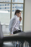 Businessman Using Mobile Phone In Office. Side view of a young businessman using mobile phone in office Stock Photo