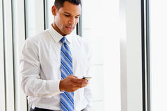 Businessman Using Mobile Phone In Office Stock Photos