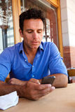 Businessman using mobile phone at outdoor cafe. Close up portrait of a businessman using mobile phone at outdoor cafe Stock Photos