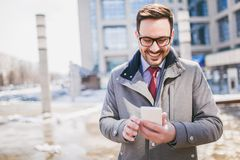 Businessman using mobile phone outside of office building. S in the background. Young caucasian man holding smartphone for business work Stock Photos