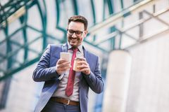 Businessman using mobile phone outside of office buildings stock image
