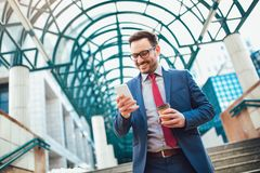 Businessman using mobile phone outside of office buildings. In the background. Young caucasian man holding smartphone for business work and drink coffee to go Stock Image