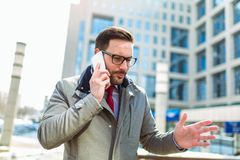 Businessman using mobile phone outside of office buildings royalty free stock images