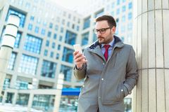 Businessman using mobile phone outside of office buildings stock images