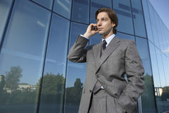 Businessman Using Mobile Phone Outside Office Stock Photo