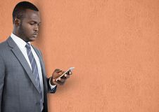 Businessman using mobile phone over peach background Royalty Free Stock Images