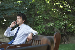 Businessman Using Mobile Phone On Park Bench Stock Photography