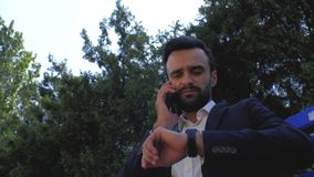 Businessman using a mobile phone in a park on a bench. man talking on a cell phone. bearded man talking on a smartphone. young stock footage