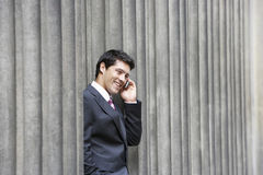 Businessman Using Mobile Phone Between Pillars Stock Images