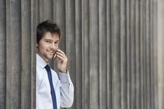 Businessman Using Mobile Phone Between Pillars Royalty Free Stock Photos