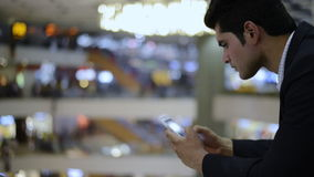 Businessman using a mobile phone in shopping mall