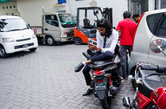 Businessman using mobile phone sitting on motorbike. Male. Maldives Royalty Free Stock Images