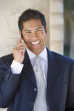 Businessman using mobile phone, smiling, close-up, front view, portrait Royalty Free Stock Images