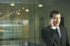 Businessman Using Mobile Phone While Standing Against Glass Wall Royalty Free Stock Photos
