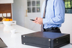 Businessman using mobile phone while standing by table Stock Images