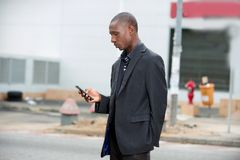 Businessman using a mobile phone in the street stock image