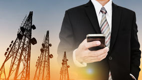 Businessman using mobile phone with Telecommunication towers with TV antennas and satellite dish in sunset. Businessman using mobile phone with Telecommunication Royalty Free Stock Photo