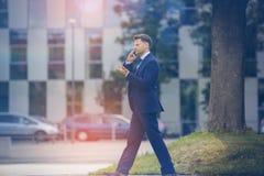 Businessman using mobile phone while walking Royalty Free Stock Photo