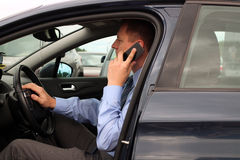 Businessman using mobile smart phone while driving the car royalty free stock photography