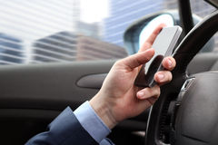 The businessman using mobile smart phone while driving the car Royalty Free Stock Image