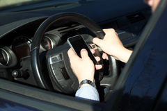 The businessman using mobile smart phone while driving the car Royalty Free Stock Photos