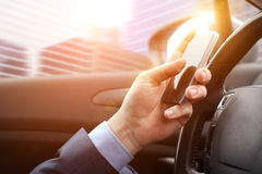 The businessman using mobile smart phone while driving the car Stock Photography