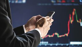 Businessman using mobile smart phone, raising graph background. Business growth, investment and invest in stock exchange market. Online stock market Stock Photo
