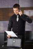 Businessman using mobile smiling Stock Image