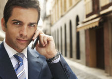 Businessman Using Mobilephone In Street. Portrait of confident young businessman using mobilephone in street Royalty Free Stock Images