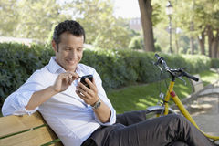 Businessman Using Palmtop Pilot On Park Bench. Happy young businessman using palmtop pilot while sitting on park bench Royalty Free Stock Images