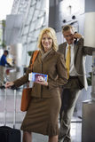 Businessman using pay phone in airport terminal, focus on businesswoman with luggage and ticket, portrait Stock Image