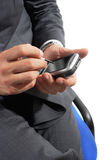 Businessman using pda. Businessman seated in a chair uses pda Royalty Free Stock Image