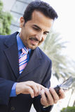 Businessman using PDA. Businessman using his PDA outside Royalty Free Stock Photos