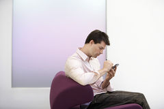 Businessman Using PDA On Sofa Stock Photo