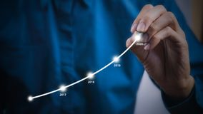Businessman using pen drawing graphics line year growing graph royalty free stock images